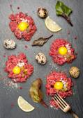 Beef tartare with egg, capers and onions on dark background — Stockfoto