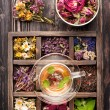 Herbal tea and dried herbs in a wooden box — Stock Photo #64243893