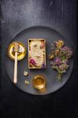 Honey and dried herbs on dark background — Stock Photo