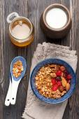 Healthy breakfast.  Oats, granola muesli, nuts, honey, dried berries and milk. Top view. — Stock Photo