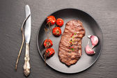 Meat Ribeye steak entrecote with roasted tomatoes and garlic — Stockfoto