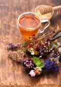 Cup of herbal tea with wild flowers and various herbs — Stock Photo