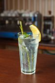 Highball glass with ice and a yellow tube on the wooden bar — Stock Photo
