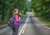 Beautiful girl with backpack walking on the road — Stock Photo
