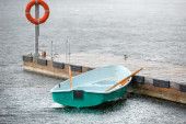 Boat under the summer rain tied to the pier — Stock Photo