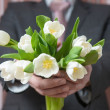 Man - businessman in a suit gives a bouquet of flowers, white tu — Stock Photo #66396959