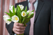 Man - businessman in a suit gives a bouquet of flowers — Stock Photo
