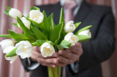 Man - businessman in a suit gives a bouquet of flowers, white tu — Stock Photo