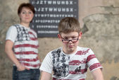 Boy measures the glasses on background mother and a table for sight check — Stock Photo