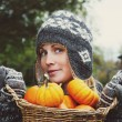 Girl holding basket of pumpkins — Stock Photo #52736673