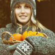 Young woman holding a basket of pumpkins — Stock Photo #52736675