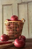 Red apples in metal basket on kitchen table — Stock Photo