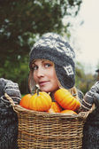Girl holding basket of pumpkins — Stock Photo