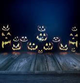 Halloween pumpkins in a dark background and wood floor — Stock Photo