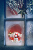 Frosted window with Christmas decoration inside — Stock Photo