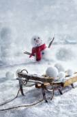 Wooden sleigh and snowballs with snowman  — Stock Photo