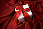 Small valentine gift on red satin — Stock Photo