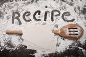 Word recipe written in white flour and spatula on wood — Stock Photo