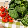 Fresh spinach leaves with tomatoes and strainer — Stock Photo #68781167