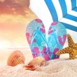 Pair of flip- flops in the sand with starfish  — Stock Photo #72265225