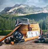 Fly fishing gear on wooden deck with lake — Stock Photo