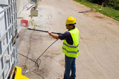 Worker in hard hat pressure washing — Stockfoto