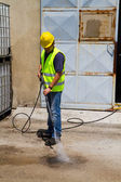 Worker in hard hat pressure washing — Stock Photo
