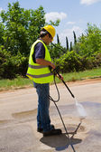 Worker in hard hat pressure washing — Foto Stock