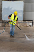 Worker in hard hat pressure washing — Fotografia Stock