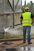 Worker in hard hat pressure washing — Stock fotografie