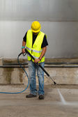 Worker in hard hat pressure washing — Foto de Stock