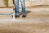 Male worker's legs with hose — Stock Photo