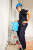 Worker paints the wal with a brush — Stock Photo