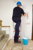 Worker paints the wall with a brush — Stock Photo
