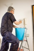 Lavoratore vernicia la parete con un rullo dell'ancoraggio — Foto Stock