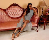Pretty African woman on pink couch. — Stock Photo