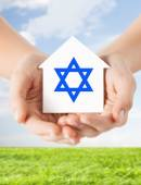Close up of hands holding house with star of david — Stock Photo