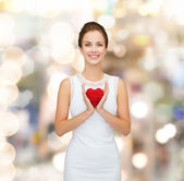 Smiling woman in white dress with red heart — Foto Stock