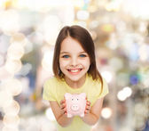 Beautiful little girl with piggy bank — Stock Photo