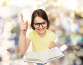 Smiling little girl in eyeglasses with book — Stock Photo
