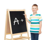 Smiling little boy with blank blackboard — Stock Photo