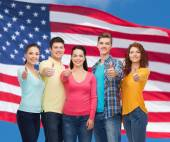 Group of smiling teenagers over american flag — Foto de Stock