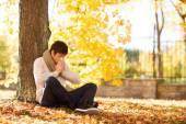 Smiling young man with tablet pc in autumn park — Stock Photo