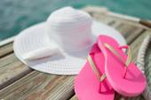 Close up of hat, sunscreen and slippers at seaside — Stock Photo
