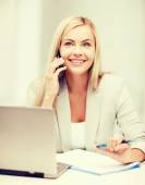 Businesswoman with laptop and cell phone — Stock Photo