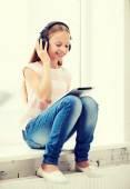 Meisje met tablet pc en hoofdtelefoon thuis — Stockfoto