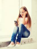 Girl with smartphone at school — Stock Photo