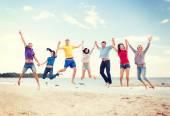 Grupp vänner hoppa på stranden — Stockfoto
