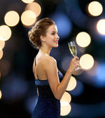 Smiling woman holding glass of sparkling wine — Stok fotoğraf