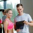 Smiling young woman with personal trainer in gym — Stock Photo #52068629